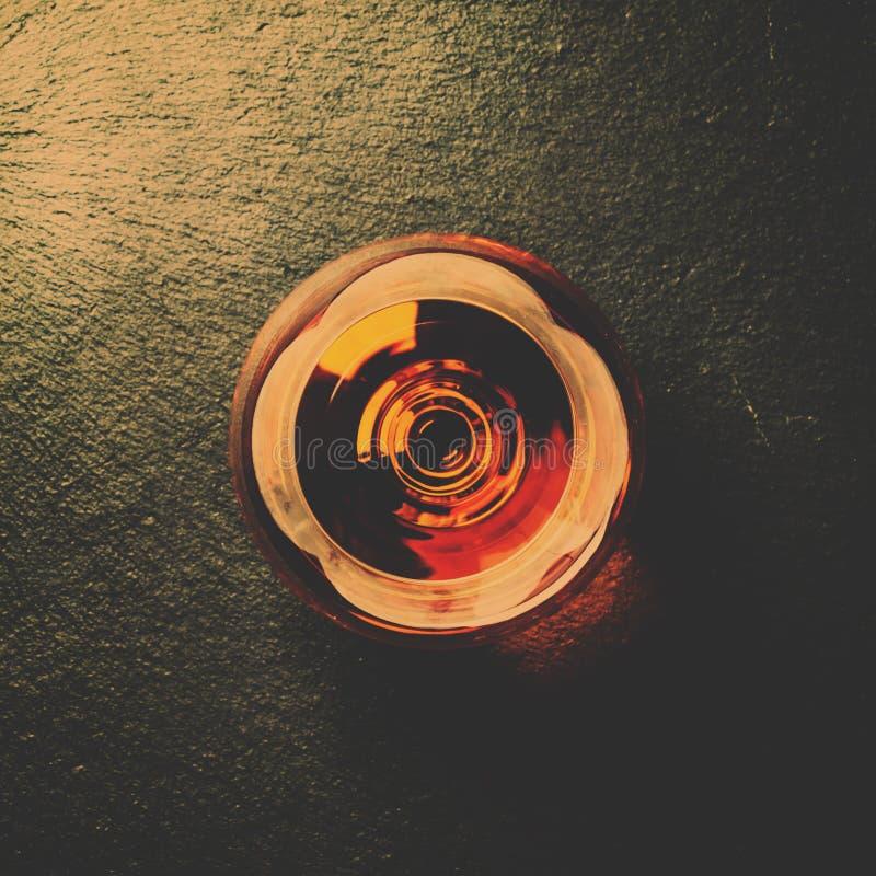 Cognac in een glas op zwarte steenachtergrond, hoogste mening en gestemd royalty-vrije stock fotografie