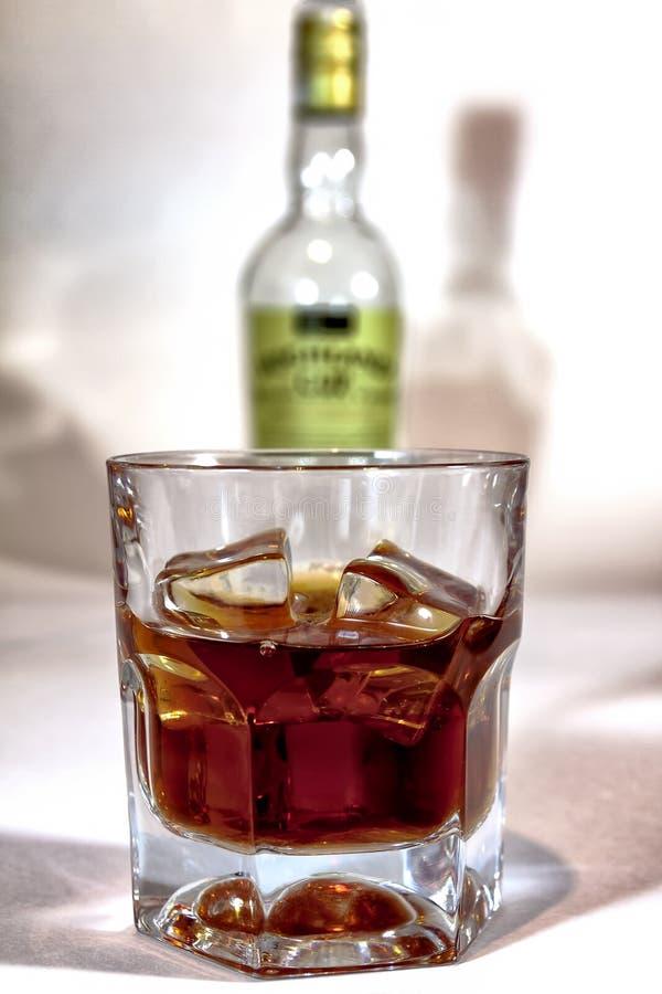 Cognac en verre sur le fond de la bouteille images libres de droits