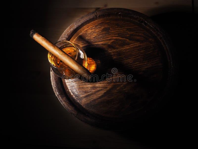 Cognac et cigare sur le vieux baril de chêne photographie stock libre de droits