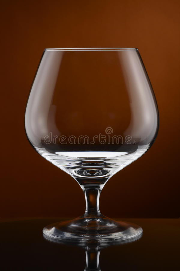 Cognac glass. Close up of empty cognac glass shot on rich amber background stock image