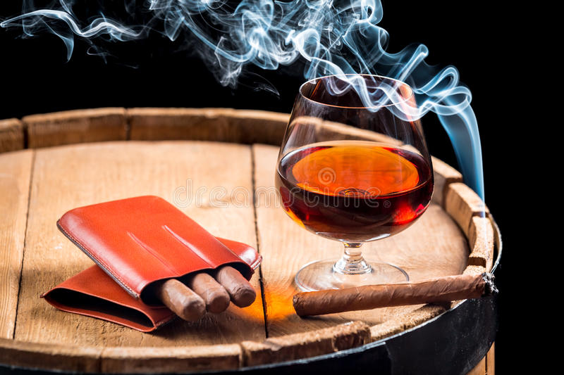 Cognac in a glass on barrel and burning cigar. Closeup of cognac in a glass on barrel and burning cigar royalty free stock photos