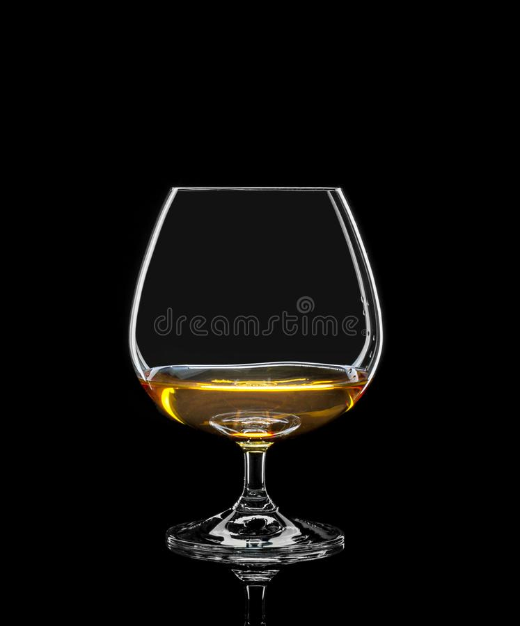 Cognac glass with drink on black. Background royalty free stock images