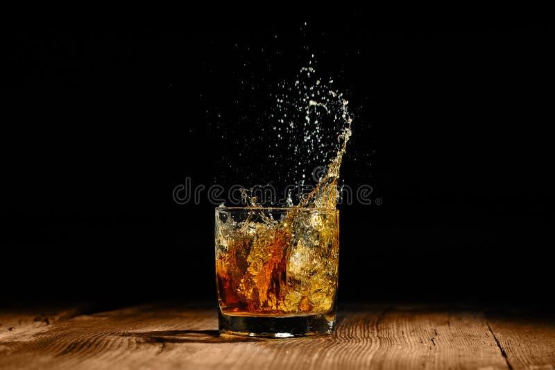 cognac splashing with ice stock photo