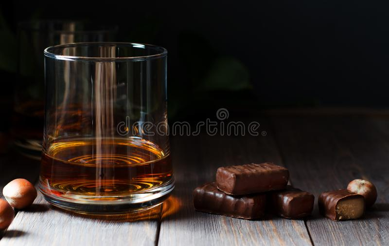 Cognac or whisky or brandy in a glass. Pieces of chocolate and hazelnuts. Dark background. Copy space. Cognac or whisky or brandy in a glass. Pieces of chocolate royalty free stock photo