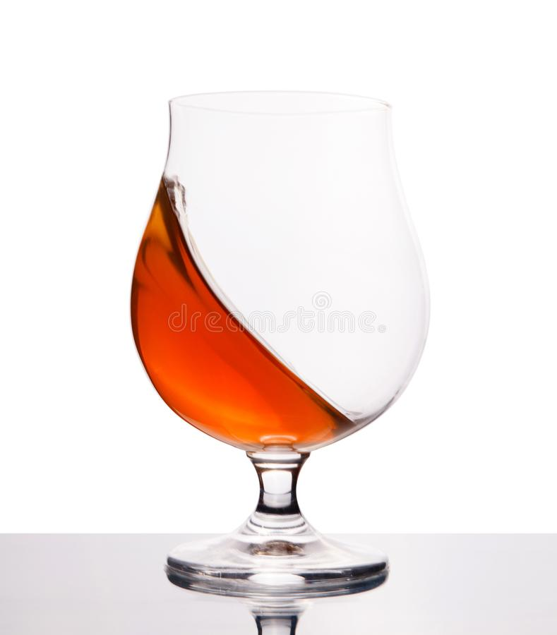 Cognac in wineglass isolated on white stock image