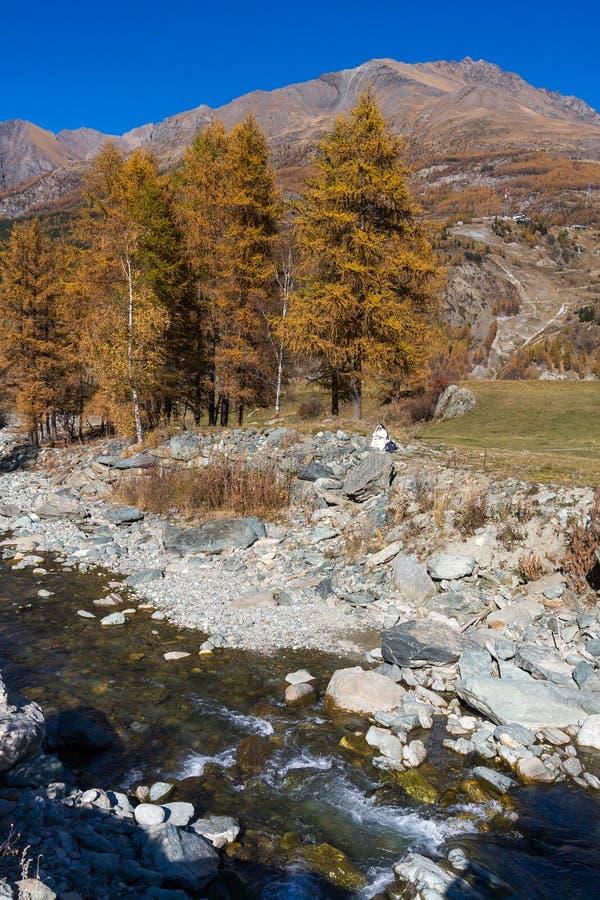 COGNE, VALLE D'AOSTA/ITALY - 26 OCTOBRE : Lecture de nonne par la rivière i image libre de droits