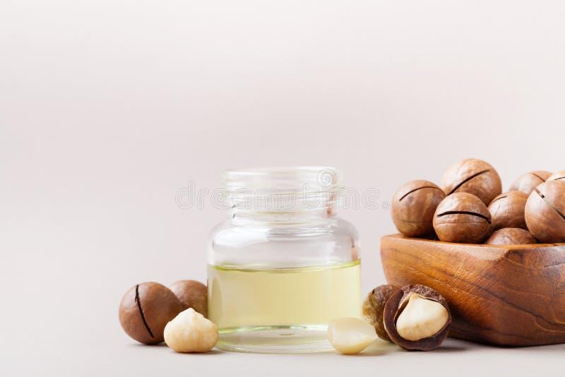 Cognez avec de l'huile et le bol de macadamia avec des écrous sur la table images libres de droits