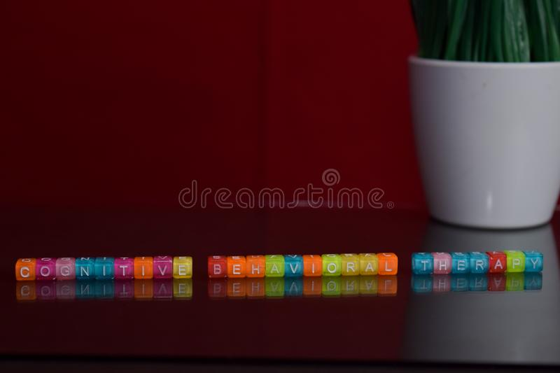 Cognitive behavioral therapy text at colorful wooden block on red background. Desk office and education concept royalty free stock photo