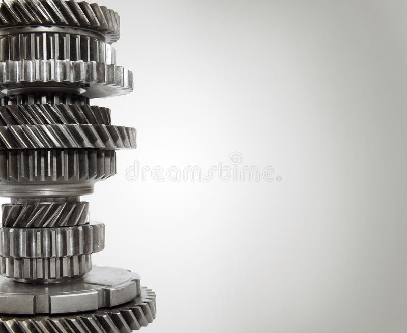 Cogs. Steel cogs together on plain background stock image