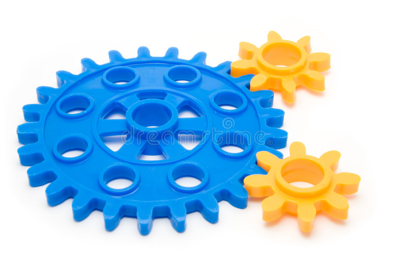 Cogs. Closeup of interlocked cogs isolated on a white background stock photo