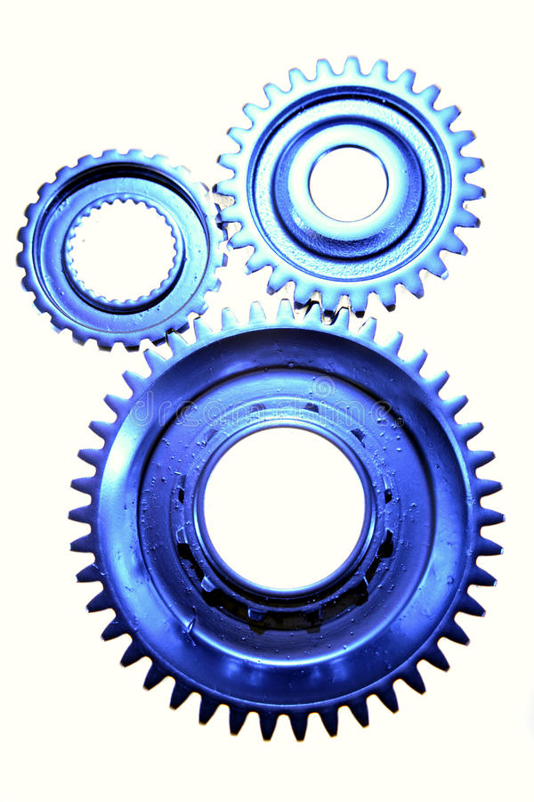 Cogs. Blue toned cog wheels isolated against a white background royalty free stock photography