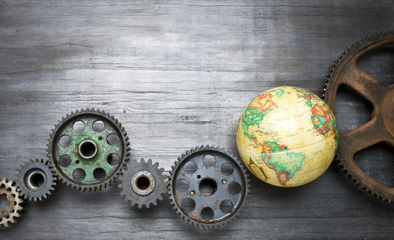 Cogs Business World Global Background Supply Chains. Old Cogs on a rustic wood background with a world globe royalty free stock photography