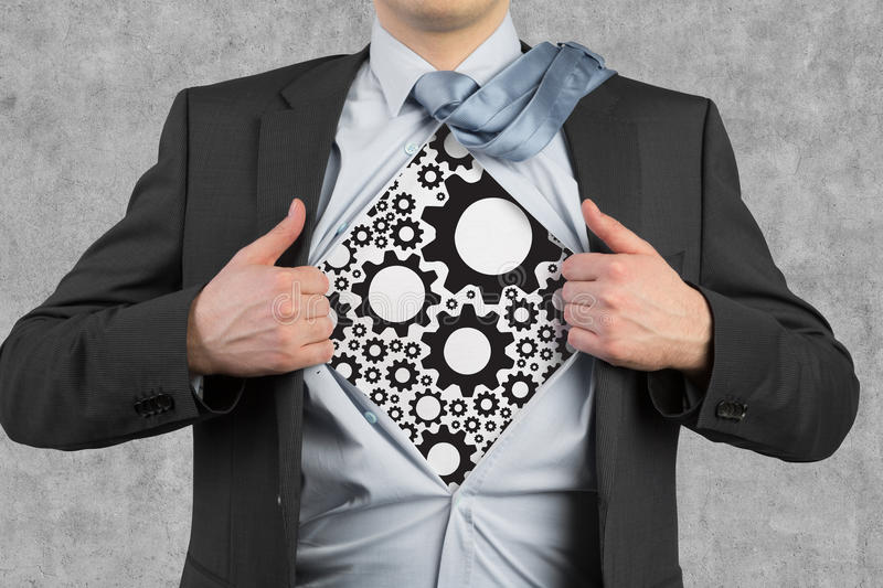 Cogs and gears. Businessman tearing his shirt, cogs and gears royalty free stock images