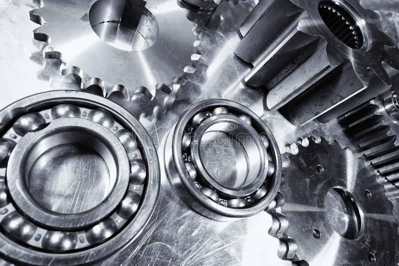 Cogs, gears, pinions and bearings. Engineering parts in titanium and steel, cogwheels and ball-bearings in wide perspective royalty free stock images