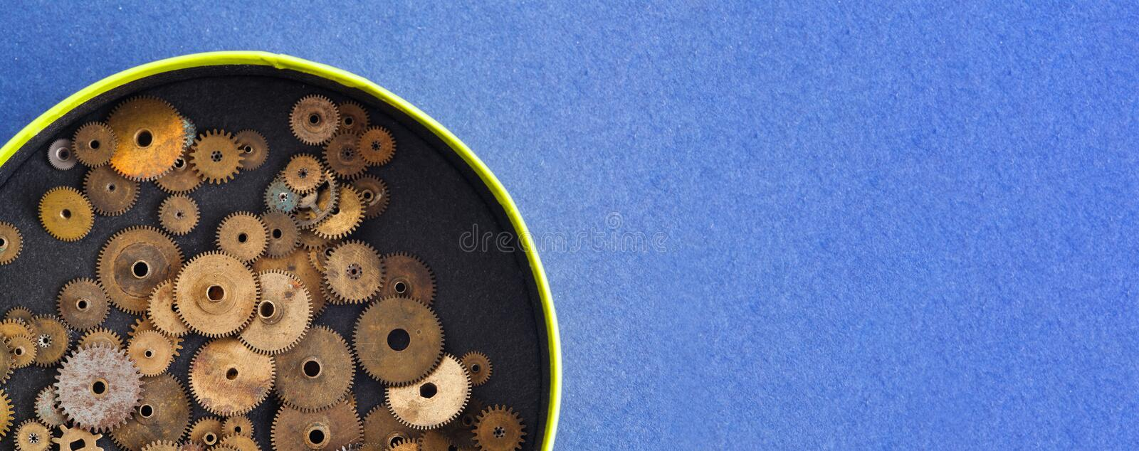 Cogs wheels gears collection in opened vintage box. macro view, blue paper background. copy space.  royalty free stock photography