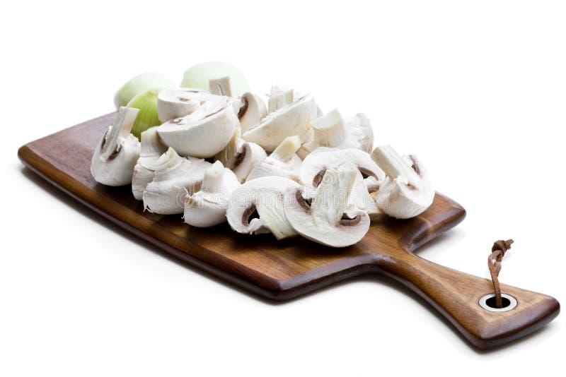 Cogumelos e cebola cortados crus na placa de corte isolada no branco fotografia de stock