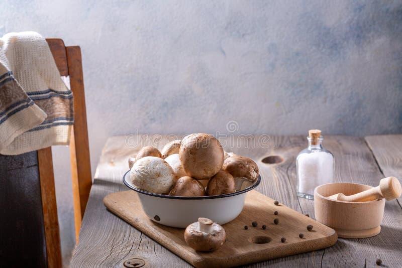 Cogumelos e especiarias de campeão sobre uma mesa de madeira Conceito de cozedura imagens de stock