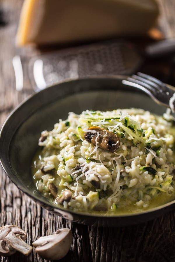 Cogumelos e Parmes?o italianos do abobrinha do risoto na placa escura imagem de stock