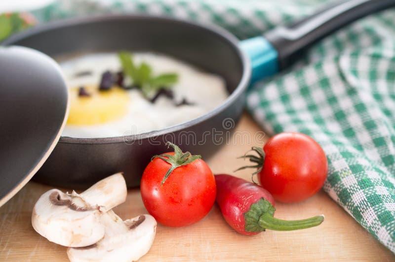 Cogumelos e pimentos frescos dos tomates ao lado de uma omeleta que frita o pa fotografia de stock royalty free