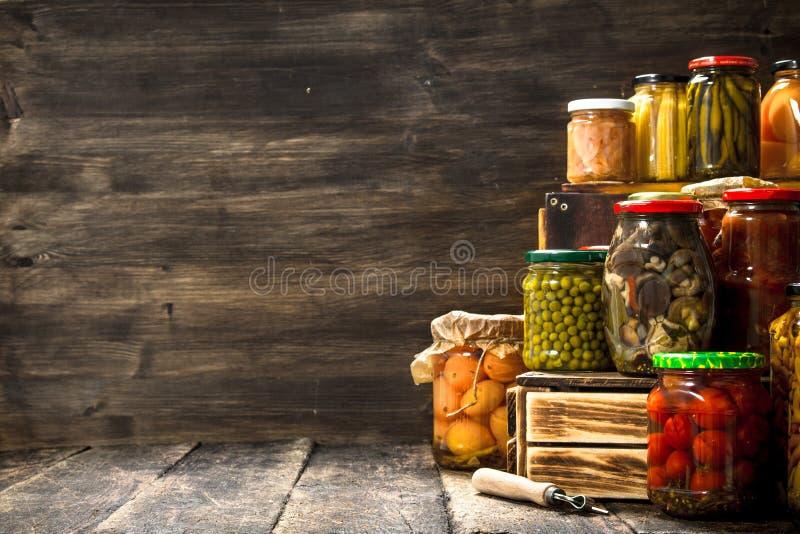 Cogumelos e vegetais das conservas em uma caixa imagem de stock
