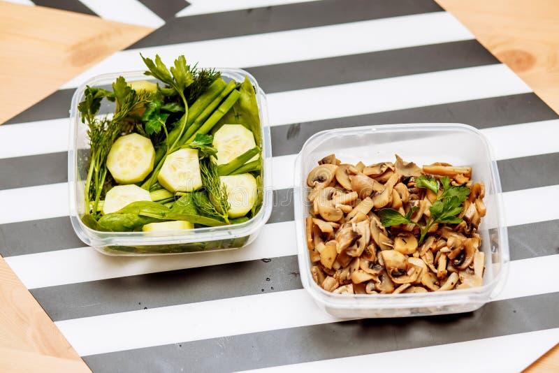 Cogumelos, ervas frescas aneto, salsa, cebolas, espinafres e partes do corte de pepinos em dois recipientes na mesa de cozinha no foto de stock