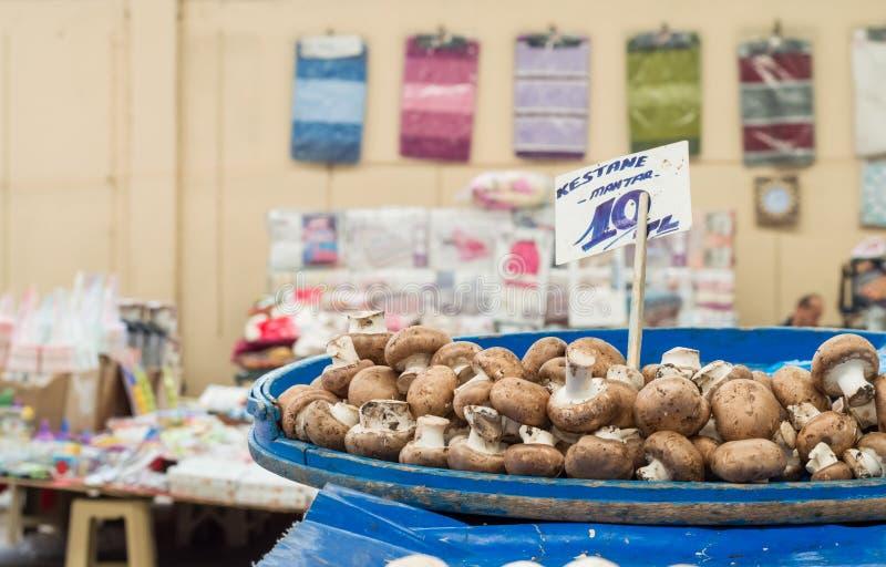 Cogumelos frescos com o preço no contador com backgound obscuro em um bazar típico do greengrocery em Turquia foto de stock