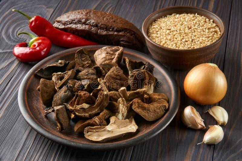Cogumelos secados e arroz integral em placas rústicas da argila imagens de stock
