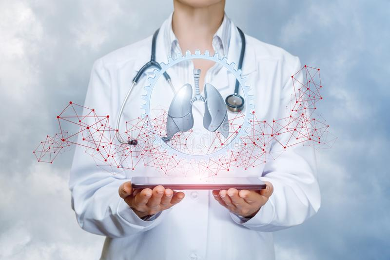 A cogwheel with lungs model inside surrounded by digital connections is hanging above a device in doctor`s hands. The concept is. The internal organs treatment stock photos