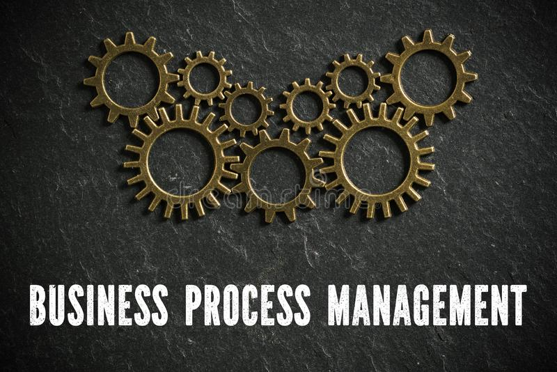 Cogwheels symbolizing complex machinery and the word `business process management `. On slate background stock photos