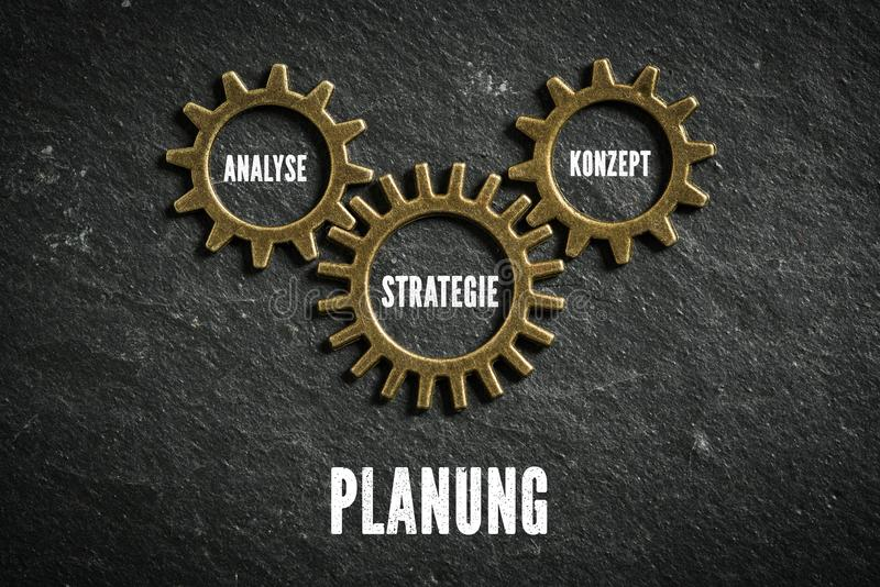 Cogwheels symbolizing connection of components of `planning` in German. On slate background stock image