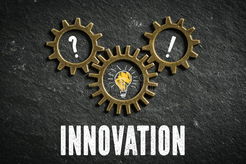 Cogwheels symbolizing a connection of topics and the message `innovation` on slate background stock photography