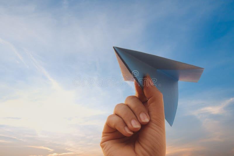 Cohete de papel azul de la tenencia de la mano de la mujer con el cielo de oro durante fondo de la puesta del sol Concepto de la  fotografía de archivo