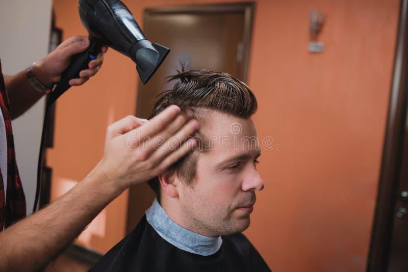 Coiffeur à l'aide du sèche-cheveux et du peigne photographie stock