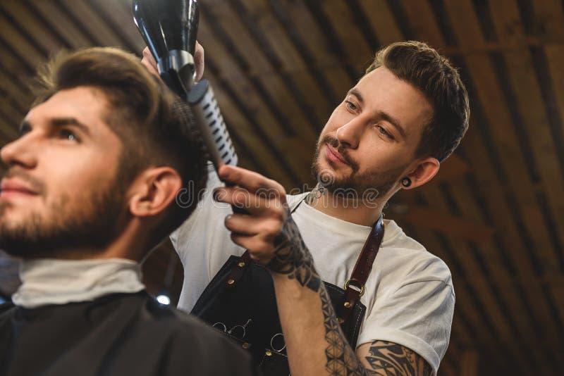 Coiffeur à la mode faisant la coupe de cheveux à l'intérieur photo libre de droits