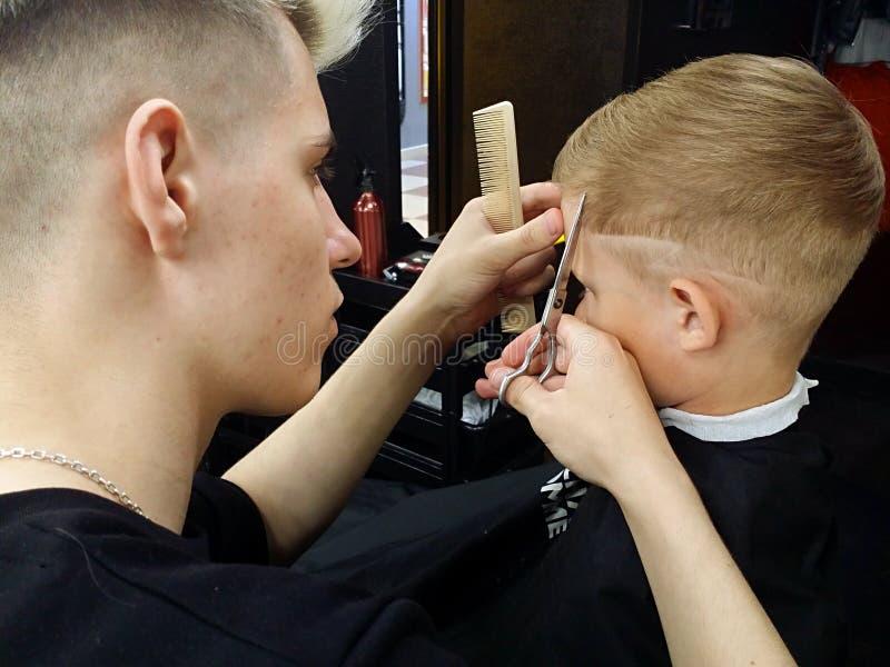 Coiffeur caucasien avec des ciseaux et des coupes de peigne le garçon dans le salon de coiffure photographie stock libre de droits