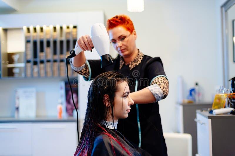 Coiffeur de femme séchant des cheveux de client avec le sèche-cheveux image libre de droits
