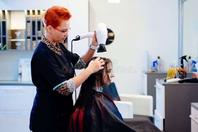 Coiffeur de femme séchant des cheveux de client avec le sèche-cheveux photos stock