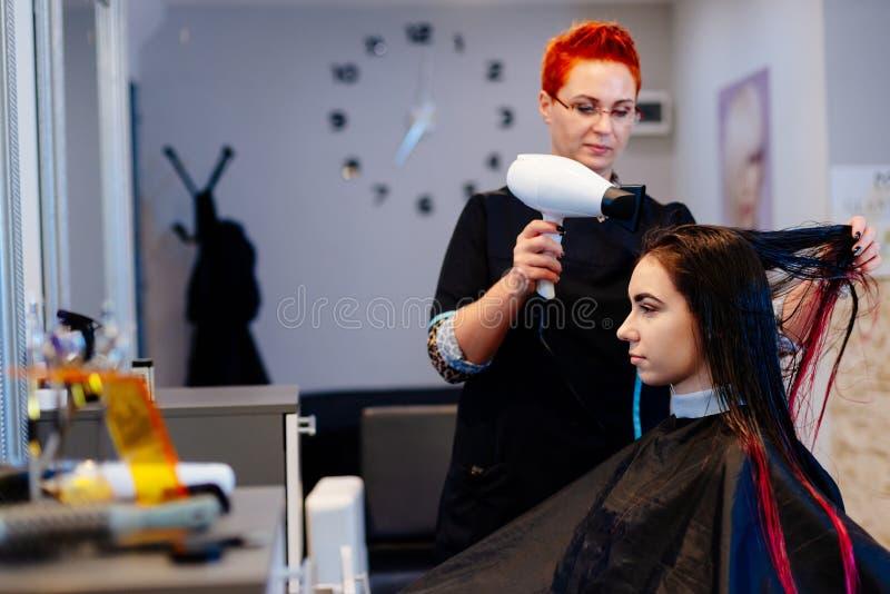 Coiffeur de femme séchant des cheveux de client avec le sèche-cheveux photo libre de droits