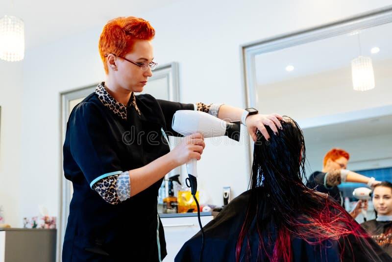 Coiffeur de femme séchant des cheveux de cliente de jeune femme dans le salon image stock