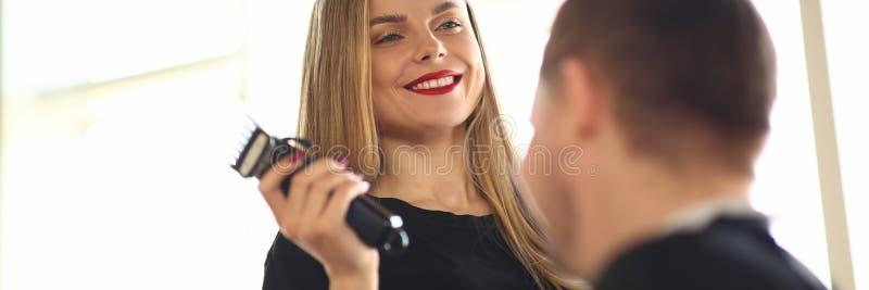 Coiffeur de sourire Using Electric Razor au client photo libre de droits