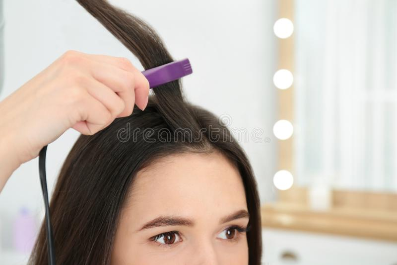 Coiffeur employant le fer plat moderne pour dénommer les cheveux du client dans le salon, plan rapproché image stock