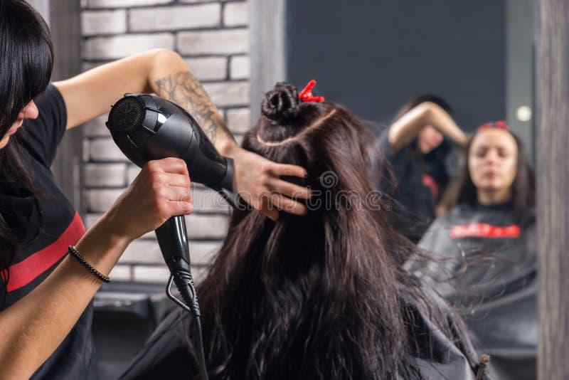 Coiffeur féminin avec les mains tatouées utilisant un sèche-cheveux sur l'ha photos libres de droits