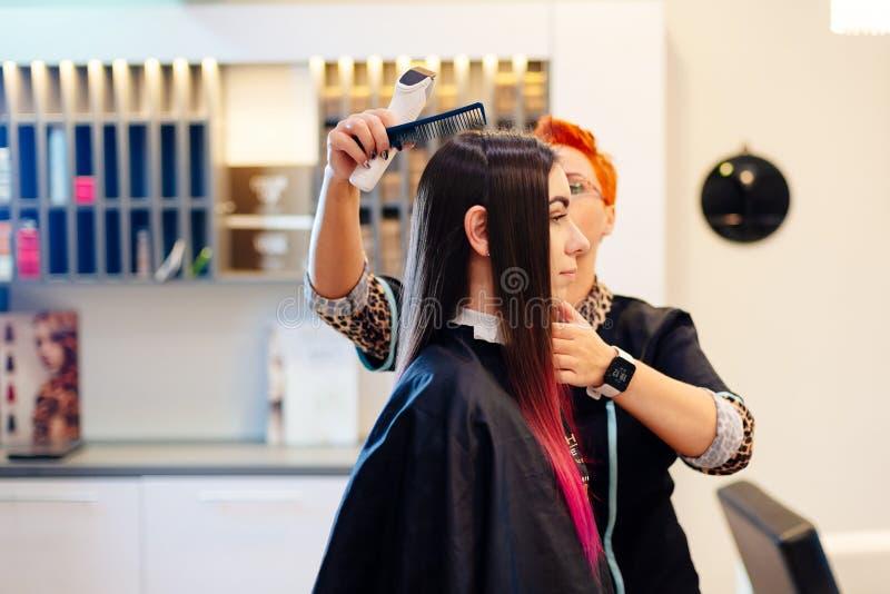 Coiffeur féminin balayant des cheveux de jeune client image stock