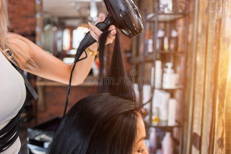 Coiffeur féminin faisant la coiffure à la fille dans le salon de beauté image libre de droits