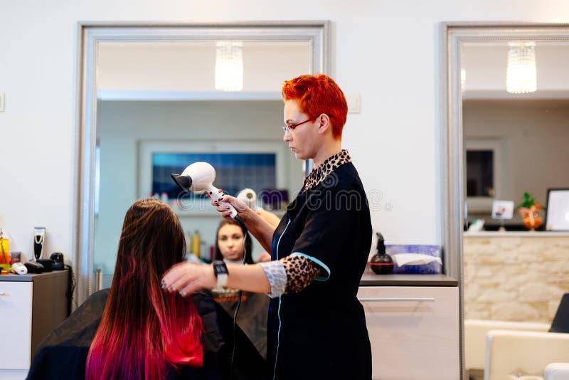 Coiffeur féminin séchant des cheveux de client avec le sèche-cheveux photographie stock libre de droits