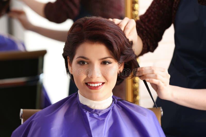 Coiffeur faisant la belle coupe de cheveux à la jeune femme image stock