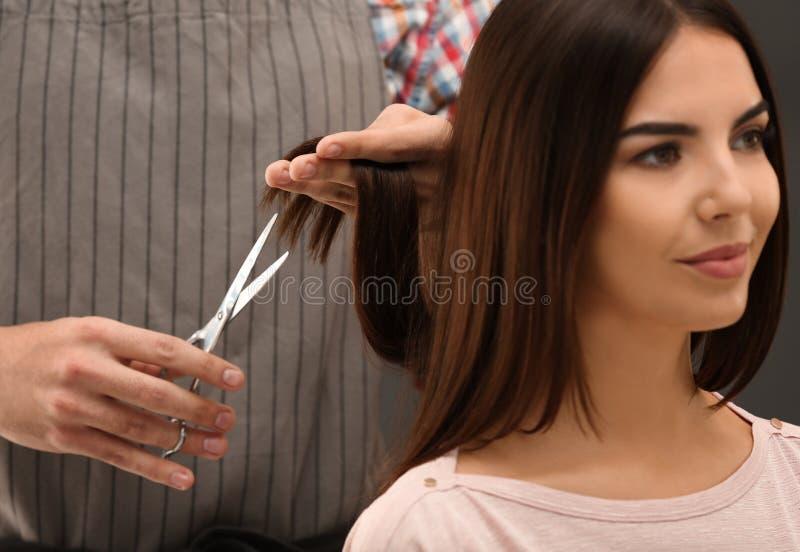 Coiffeur faisant la coupe de cheveux élégante avec des ciseaux professionnels photos stock