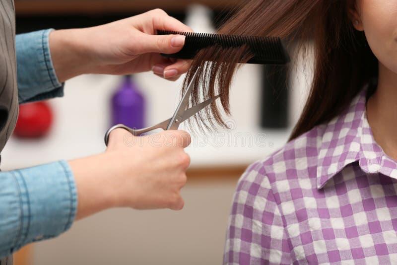 Coiffeur faisant la coupe de cheveux élégante avec des ciseaux professionnels dans le salon de beauté image libre de droits