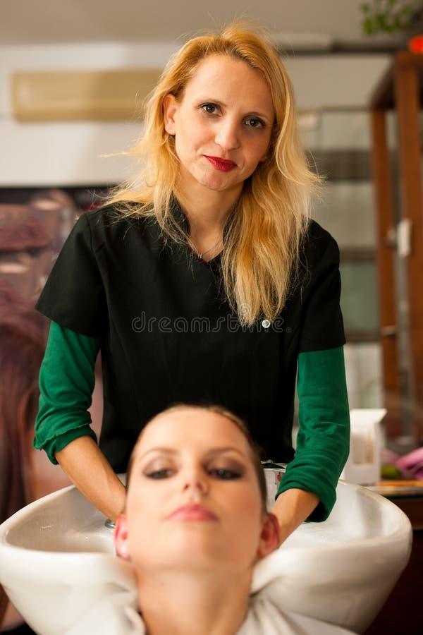 Coiffeur faisant le traitement de cheveux à un client dans le salon images stock