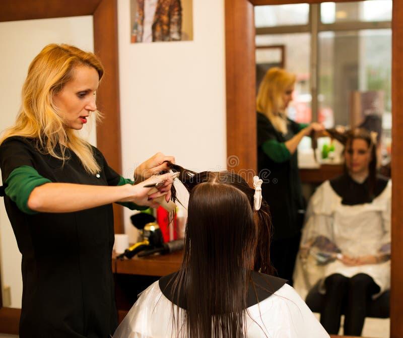 Coiffeur faisant le traitement de cheveux à un client dans le salon images libres de droits